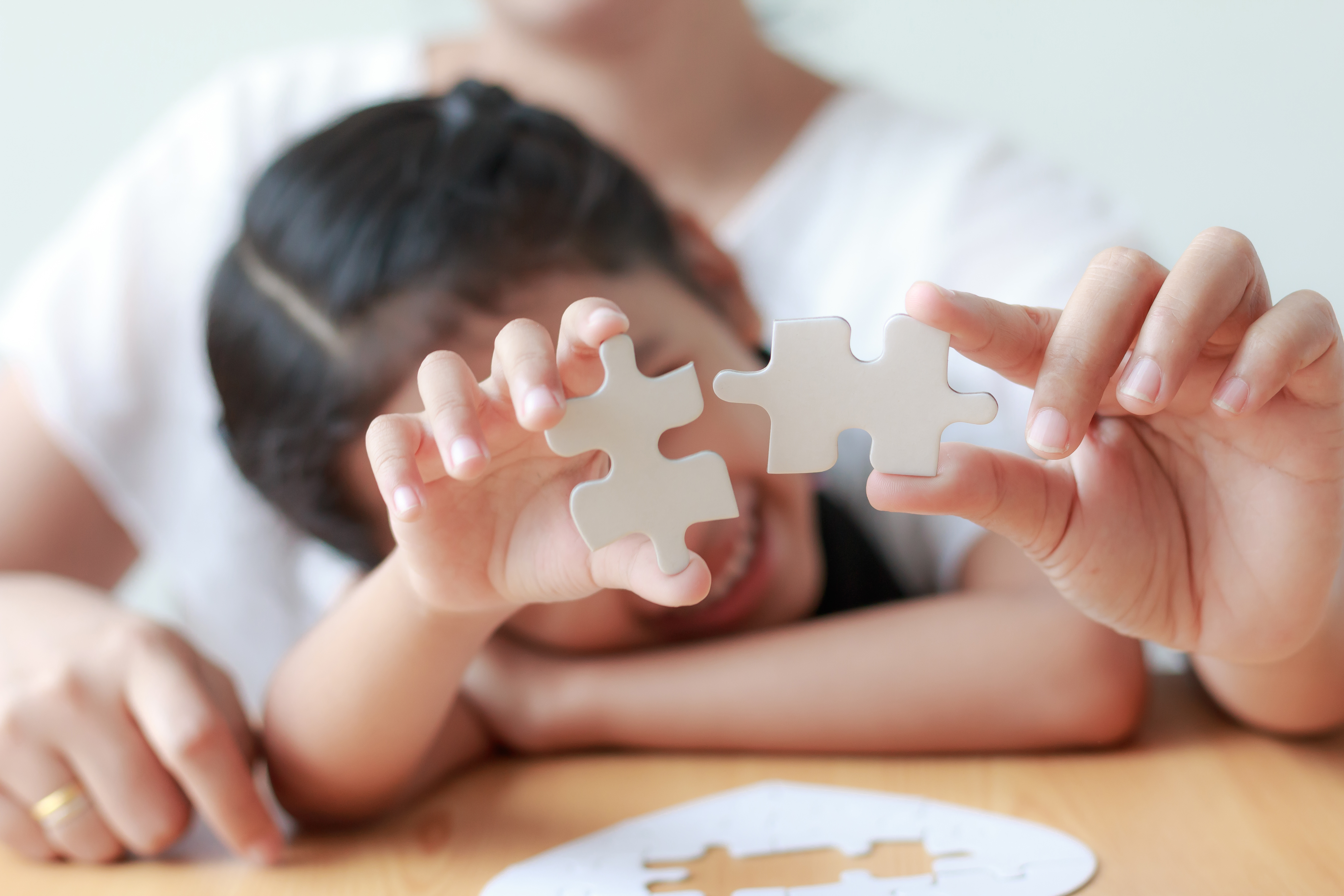 Asian little girl playing jigsaw puzzle with her mother for family concept shallow depth of field select focus on hands